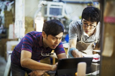 Two men using a laptop computer, working together in a glass maker's workshop.