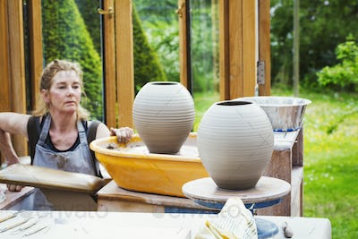 A potter examining her prefired clay pots drying before kiln firing.