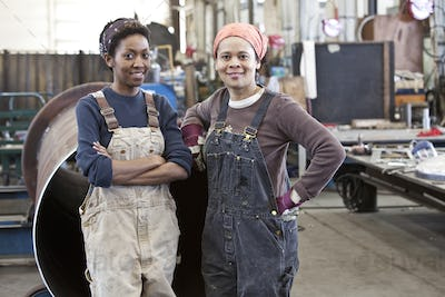 Black women team of factory workers in a sheet metal factory.