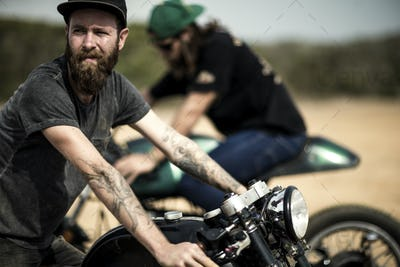 Side view of bearded man with tattoos on his arm sitting on cafe racer motorcycle on a dusty dirt