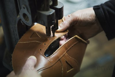 Close up of worker in a shoemaker's workshop, using a machine to punch holes into a leather shoe.