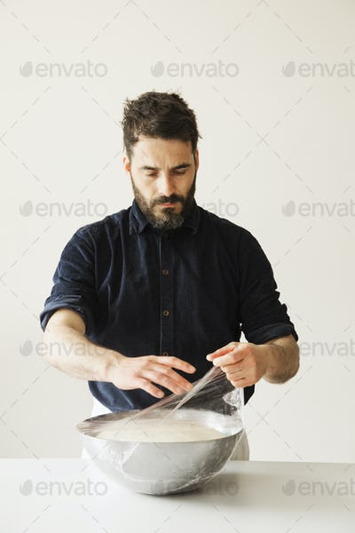 Baker covering bread dough in a metal bowl with cling film.