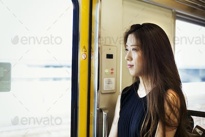 Woman with long brown hair traveling on public transport.