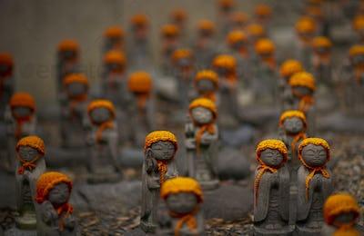 Close up of small brown Buddhist Jizo, Japanese stone statues, wearing orange hats, at Daienji,