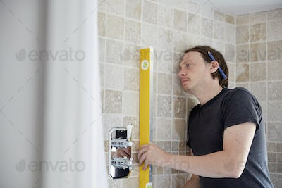 A builder using a spirit level to check his work on a wall of tiles, refurbushing a bathroom.