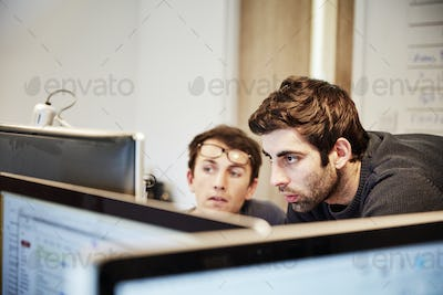 Two people, men looking at a computer screen, working together.