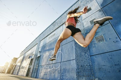 Low angle view of female athlete running along sidewalk past blue building covered in graffiti.