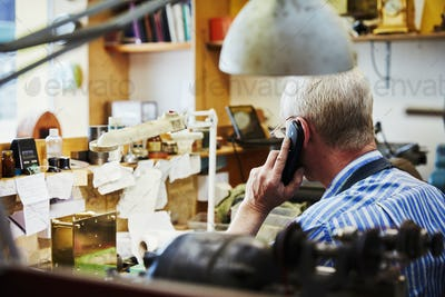 A clock maker on the telephone in his workshop.