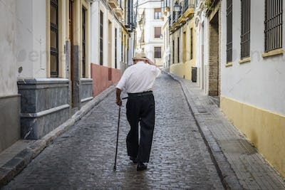 Rear view of elderly man with cane walking along cobbled street in Sevilla, Andalusia, Spain.