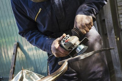 Man standing outdoors working on a metal pitchfork with a hand held electric angle grinder.