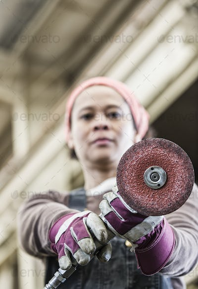 Black woman factory worker using a metal grinding tool in a sheet metal factory.