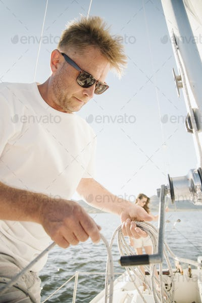 Portrait of a blond man with sunglasses on a sail boat.