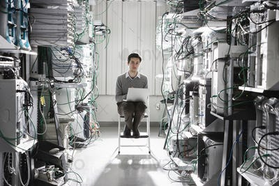 Caucasian male technician working on computer servers in a computer server farm.