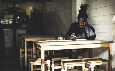 Man with dreadlocks sitting indoors at a table, looking at smartphone, beer bottle on the table.