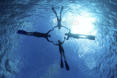 Snorkelers  playfully perform water acrobatics in the Caribbean Sea, Grand Cayman, Cayman Islands