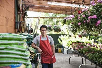 Young man employee in a red apron leaning against bags of compost at a garden center nursery.