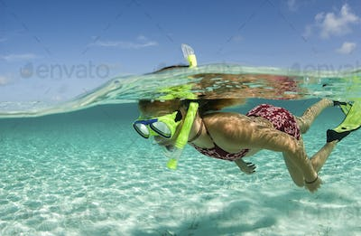 Young girl propels herself through the clear waters of the Exuma Cays.