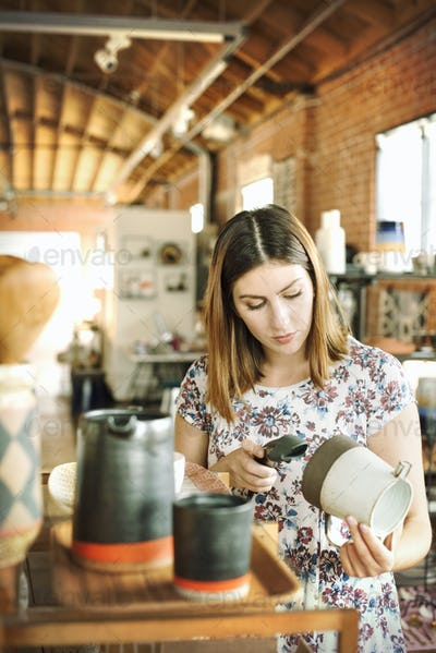 Young woman in a shop, scanning the barcode of a ceramic jug with a barcode scanner.
