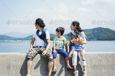 Family, man, boy and woman with young girl on her lap sitting side by side on a wall by the ocean.