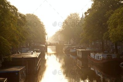 House boats moored on tree-lined canal at sunrise.