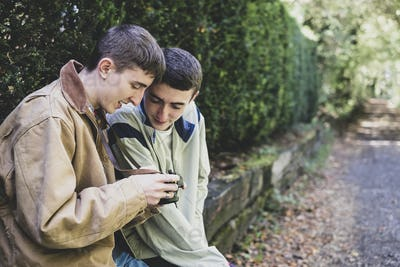 Young man and teenage boy with short brown hair wearing casual jackets sitting on hedged stone wall,