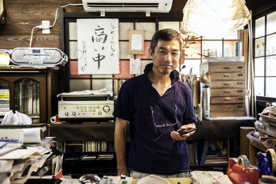 Japanese man standing in a Washi producing workshop holding a smart phone, smiling at camera.
