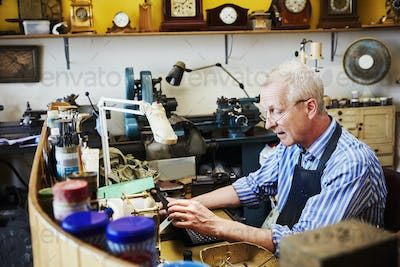 Clock repairer, a craftsman in his workshop using a laptop.