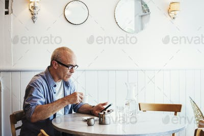 A man seated at a table checking his smart phone.