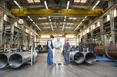 Mixed race team of workers and management people in a large sheet metal factory