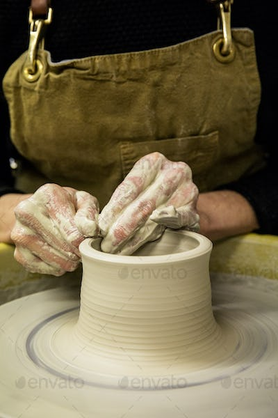 Close up of potter wearing apron working on pottery wheel, shaping clay vase.
