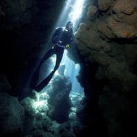 Crepuscular rays illuminate a scuba diver at Coral Caverns dive site.,Diver in Reef Crevice.