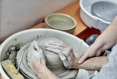A person seated at a potter's wheel turntable, with hands on a wet clay lump, being taught to handle