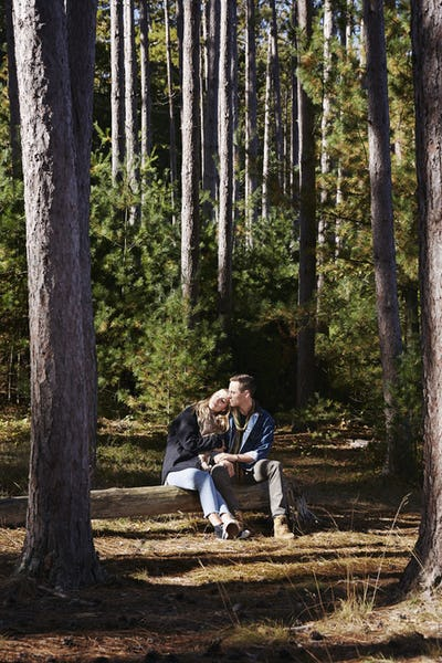 A couple seated ona log in a pine forest.