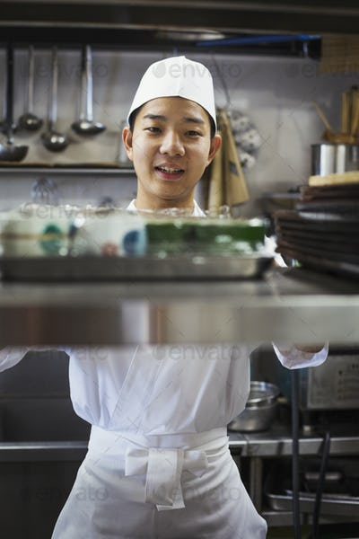 Chef working in the kitchen of a Japanese sushi restaurant.