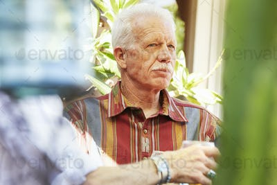 Senior man with moustache sitting outdoors.