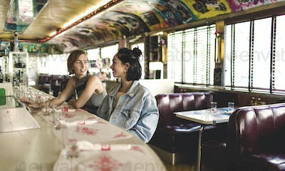 Two young women sitting side by side at a bar counter in a diner.