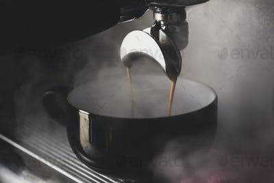 Close up of black mug on espresso machine, hot coffee pouring from spout.