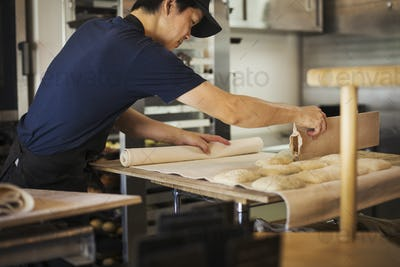 Man working in a bakery, cutting dough for rolls with large cutter.