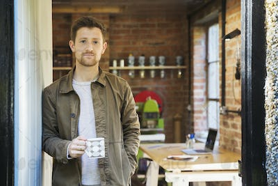 A young man standing at a workshop door, holding a coffee cup.