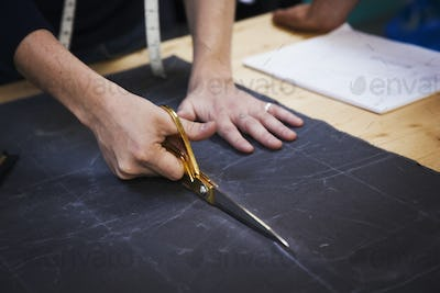 A man cutting a piece of grey fabric with shears.