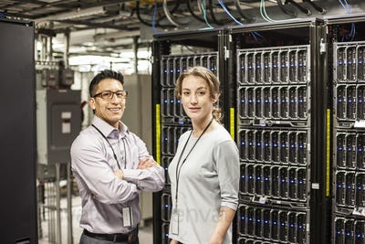 Caucasian man and woman technicians in a large computer server farm.