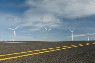Wind turbines, tall white towers in the flat plains by a road near the Columbia River Gorge.
