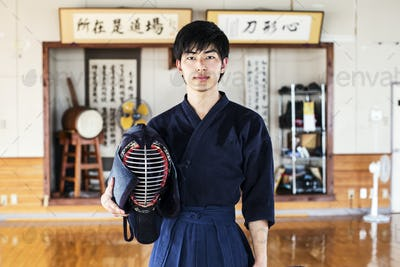 Male Japanese Kendo fighter standing in a gym, holding Kendo mask, looking at camera.