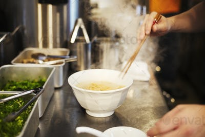 A ramen noodle shop kitchen. A chef preparing bowls of ramen noodles in broth, a speciality and fast