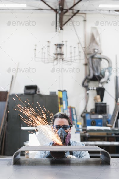Woman wearing safety glasses and dust mask standing in metal workshop, using power grinder, sparks