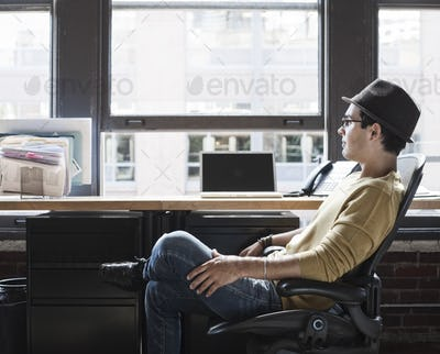 Hispanic male at his office workstation in a creative office.