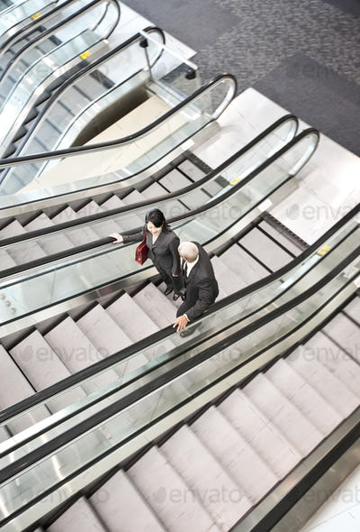 Mixed race pair of business people on the way to a meeting near a set of escalators.