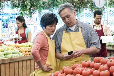 man and woman wearing aprons standing at stall with fresh tomatoes at a fruit and vegetable market.