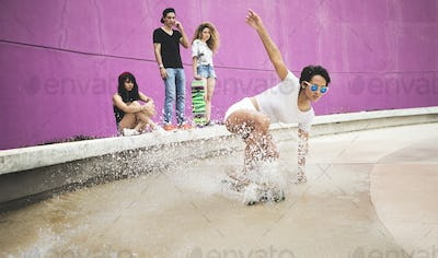A young woman crouching down riding a skateboard through water.