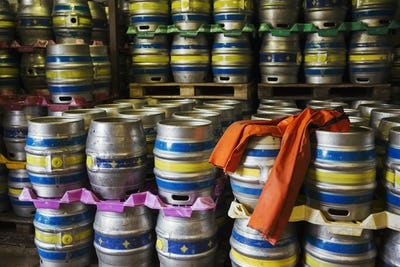 Stacks of metal beer kegs in a brewery.